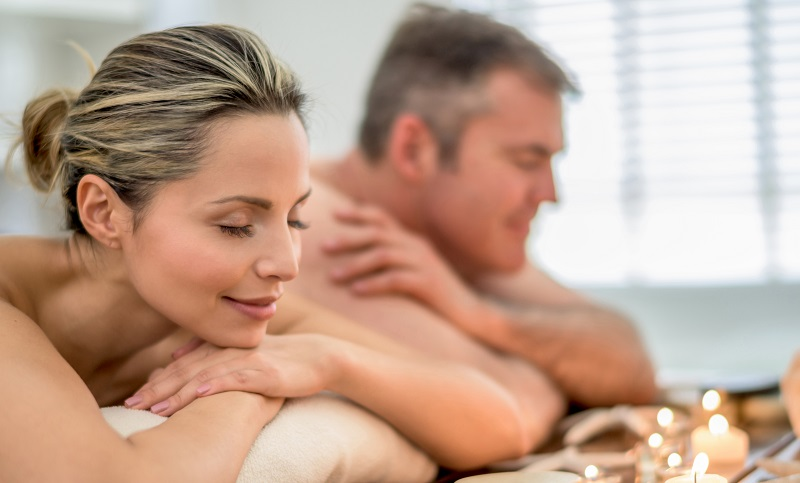 Loving couple relaxing at the spa and celebrating their anniversary with a massage